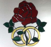 stained glass rose with wedding rings